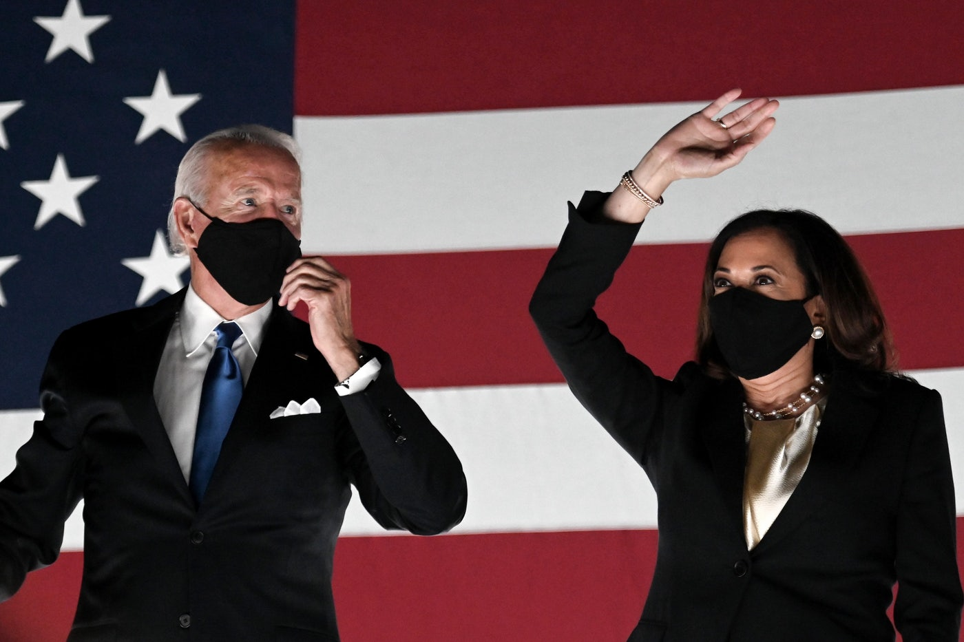 Joe Biden and Kamala Harris stand in front of an American flag backdrop