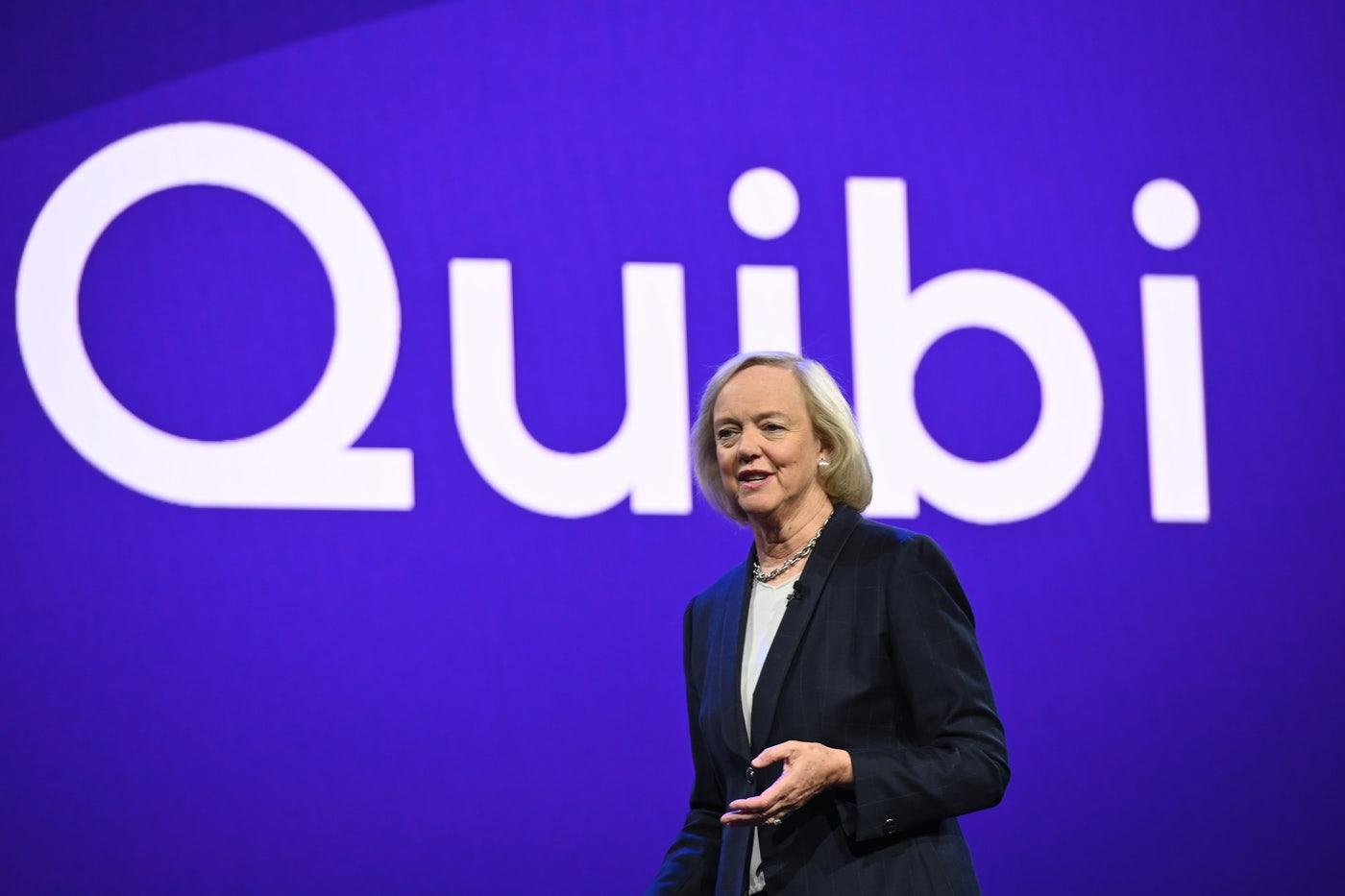 "Quibi CEO Meg Whitman stands before a banner that reads ""Quibi"""