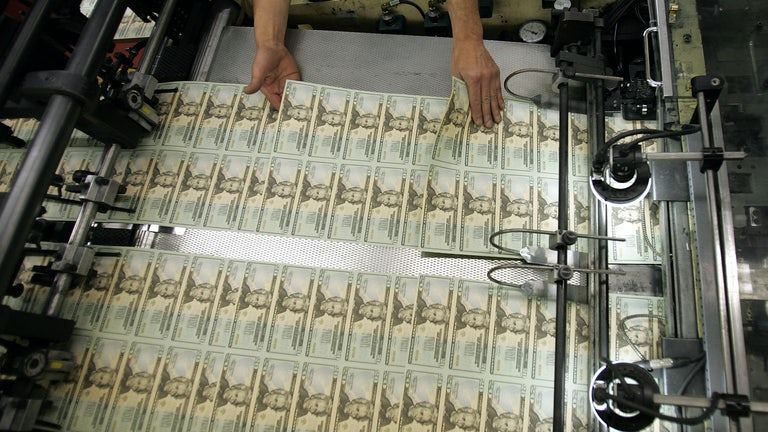 A worker's hands hover over recently printed twenty-dollar bills, inspecting them.