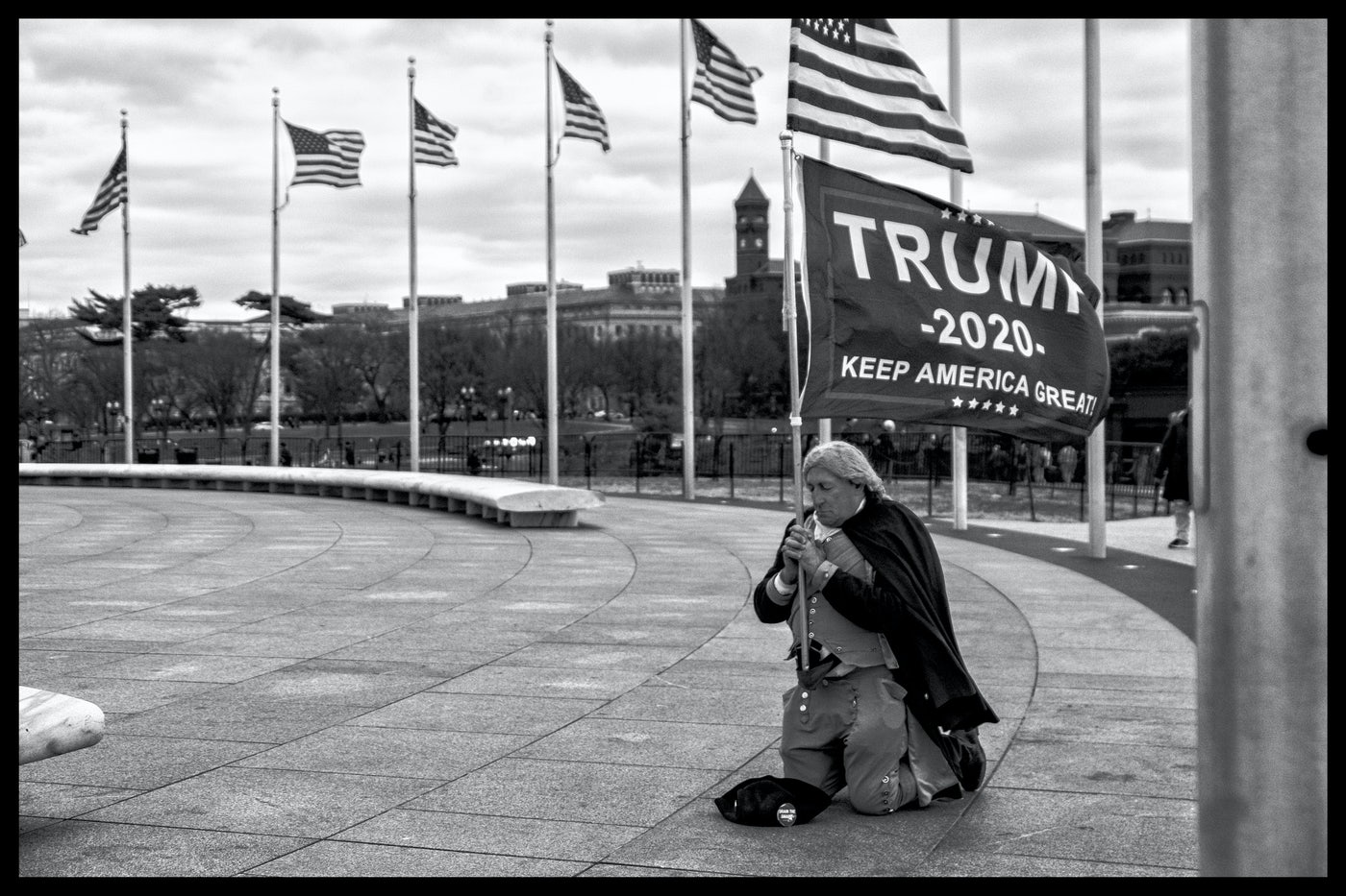A man in a Revolutionary War costume kneels on the ground, clutching a Trump banner.