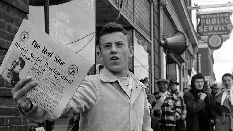 A man selling newspapers during the Mock Communist Invasion of Mosinee, Wisconsin, May 1950.