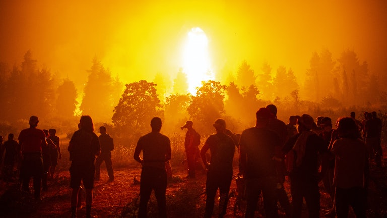 People stand in front of a raging wildfire.