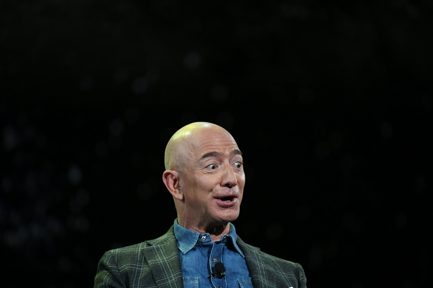 Jeff Bezos, against a black backdrop, looks surprised and excited