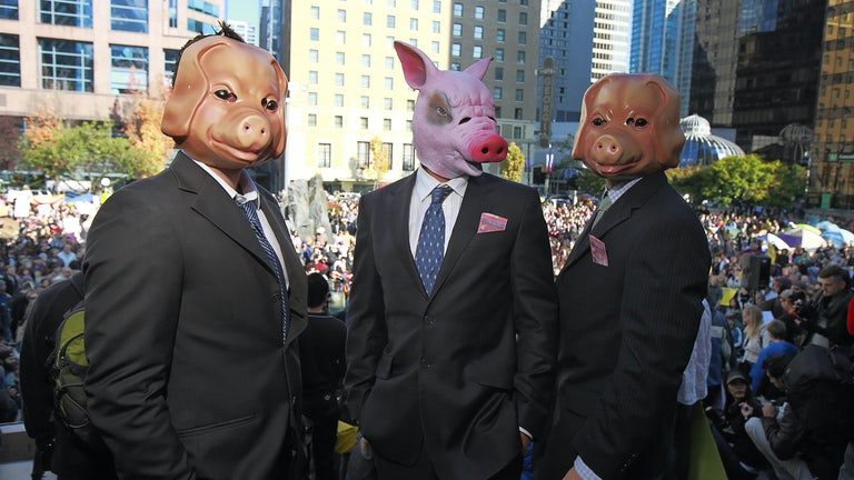 Activists wear pig masks to protest Wall Street greed.
