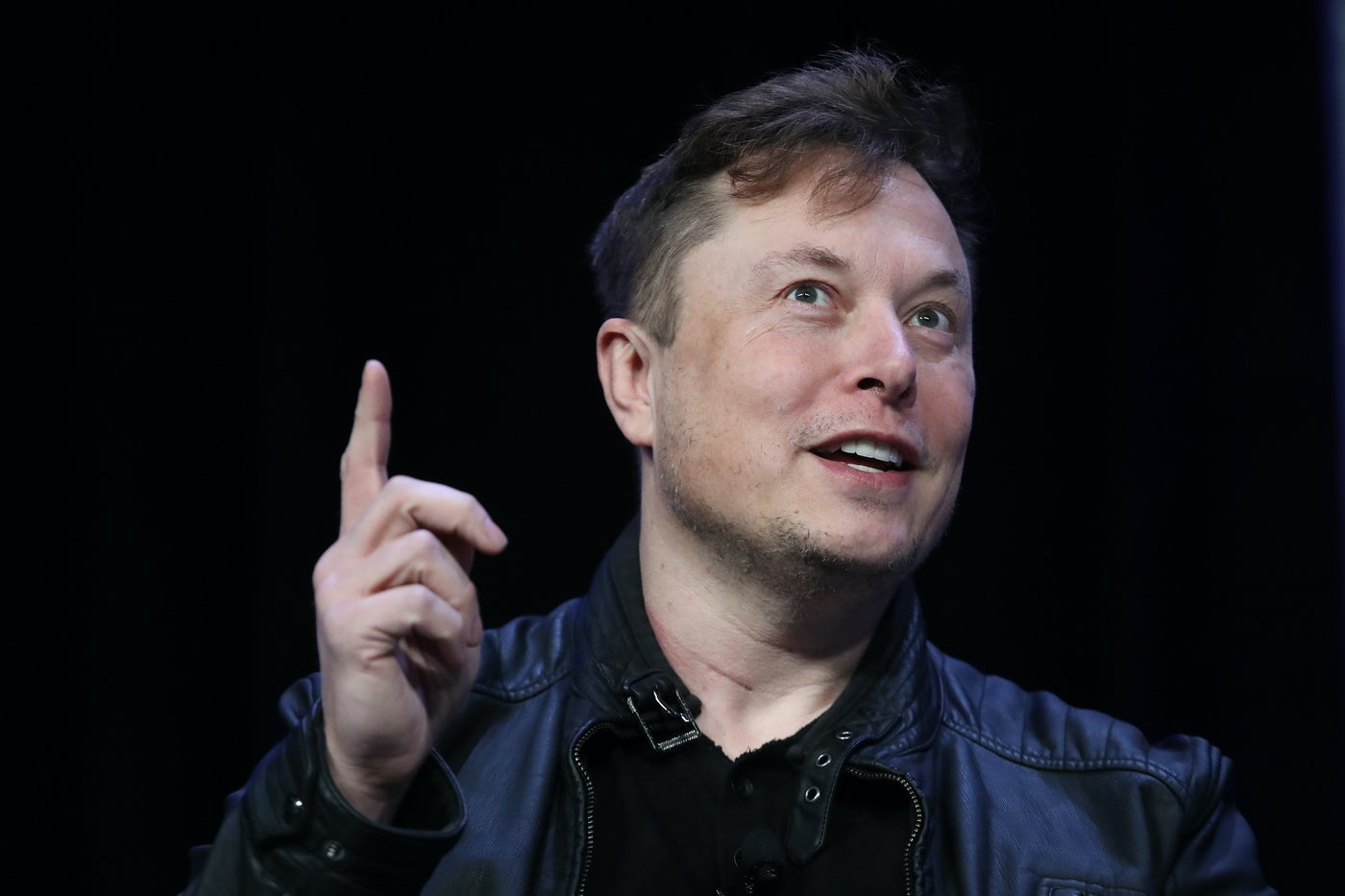 Elon Musk smiles, points a finger upwards