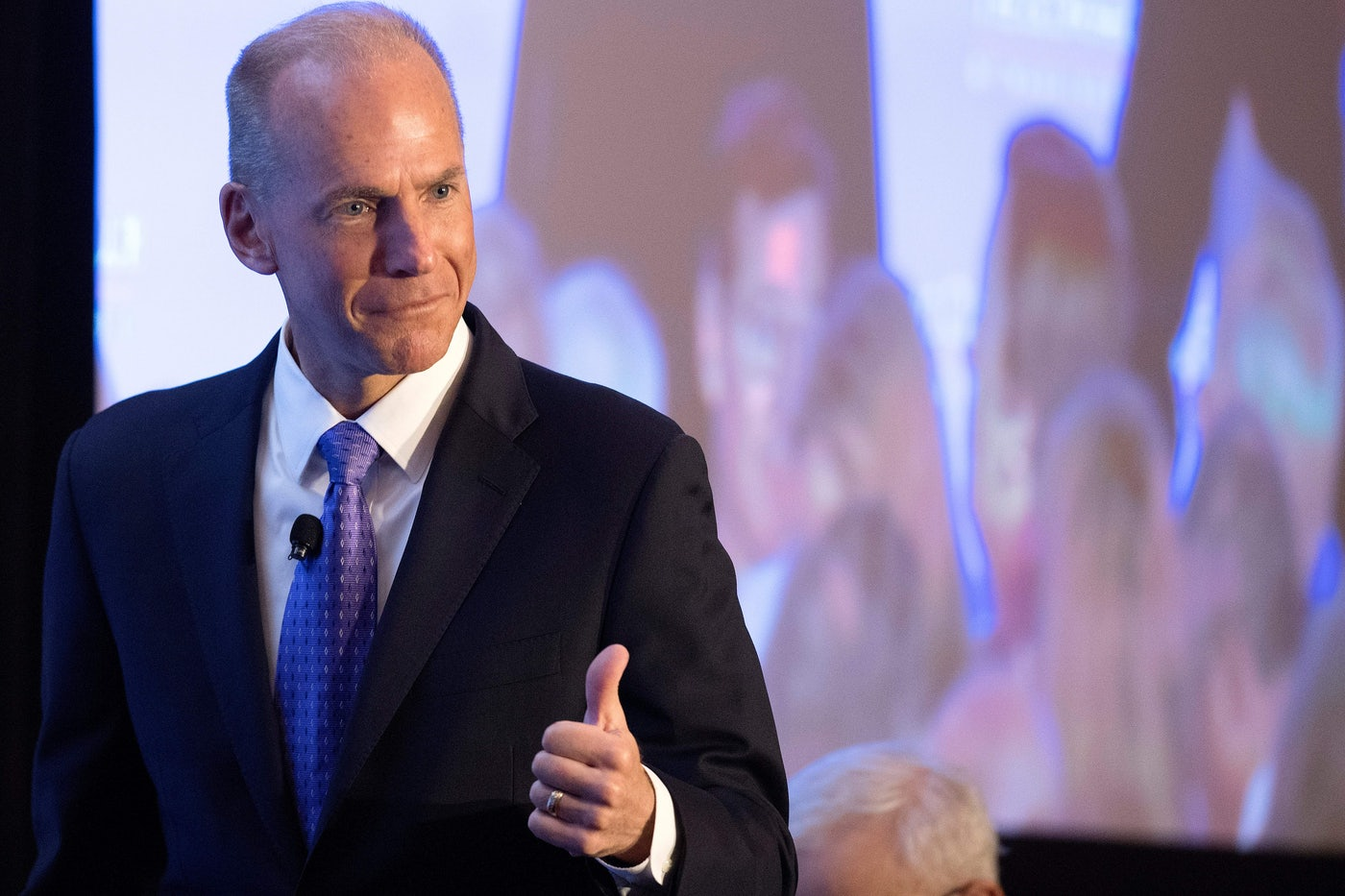 Former Boeing CEO Dennis Muilenburg gives a thumbs up gesture in front of a screen.
