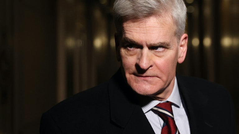 Louisiana Senator Bill Cassidy glowers in a dark hallway.