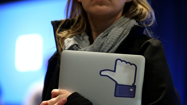 "A Facebook employee holds a laptop with a ""like"" sticker on it."