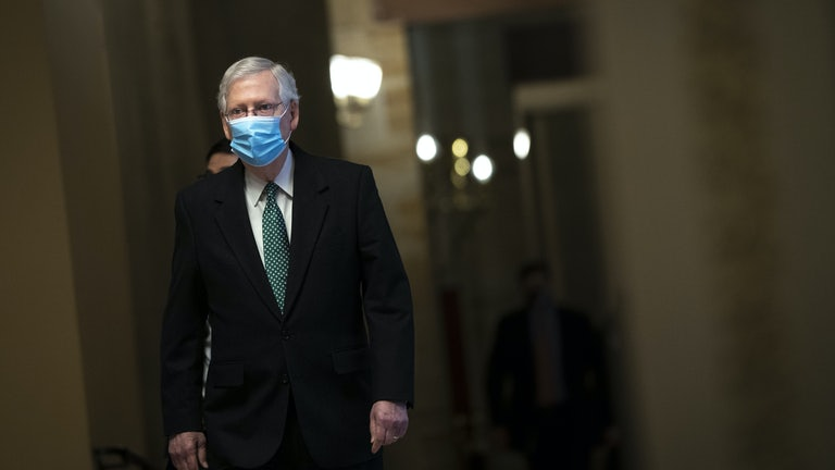 Minority Leader Mitch McConnell walks to the Senate Chamber wearing a mask.