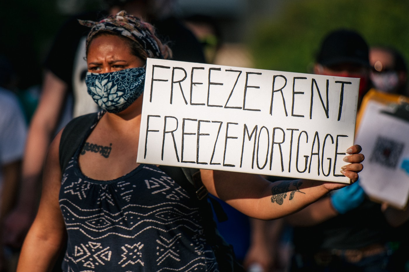 "A woman at a protest holds a sign that reads ""Freeze Rent, Freeze Mortgage."""