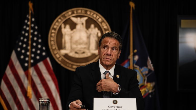 New York Governor Andrew Cuomo speaks at a news conference with flags and a state seal behind him.