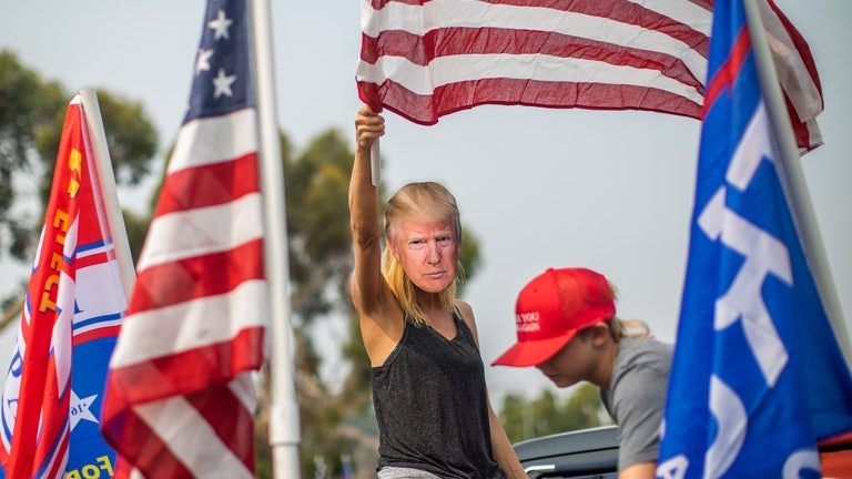 A woman wearing a Trump mask waves an American flag at a rally.