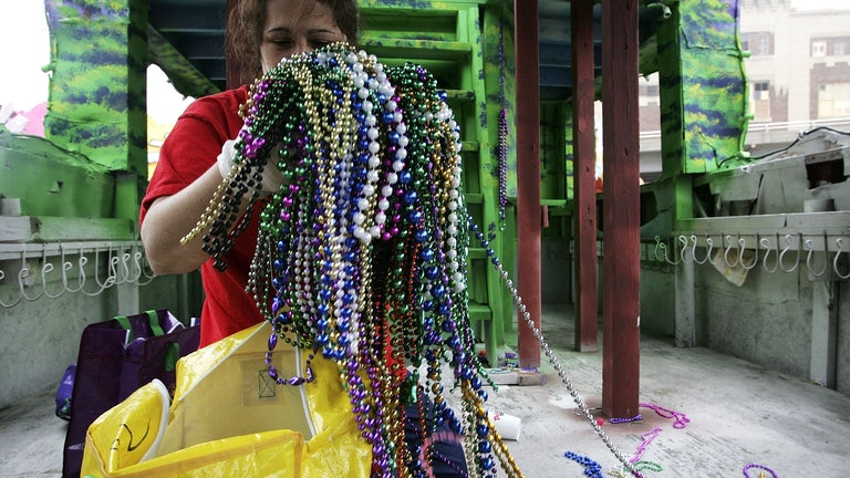 A worker holds a huge mass of Mardi Gras beads.