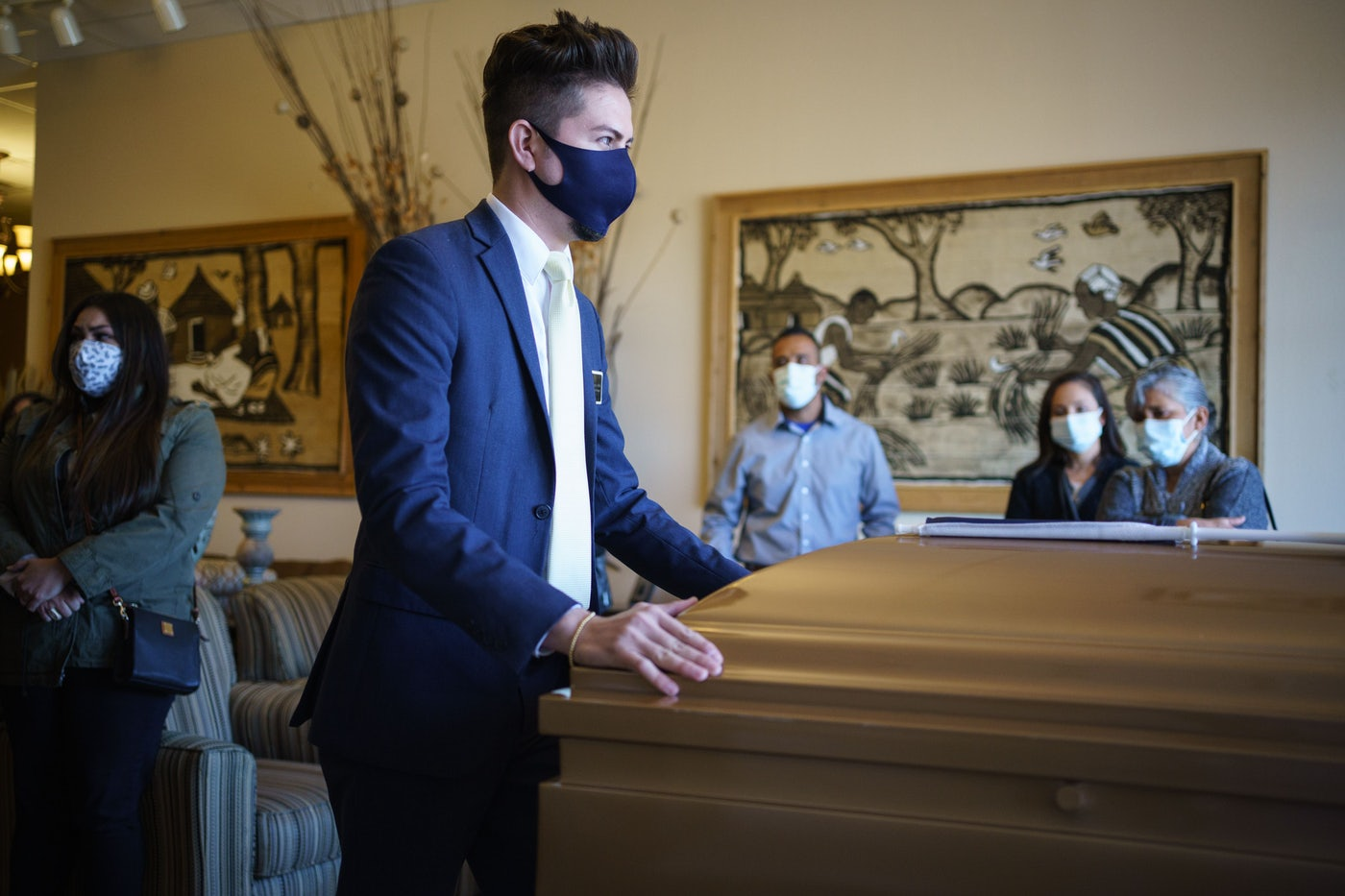 The manager of Perches Funeral Home pushes the casket of Humberto Rosales, a care provider who died of Covid-19 complications.
