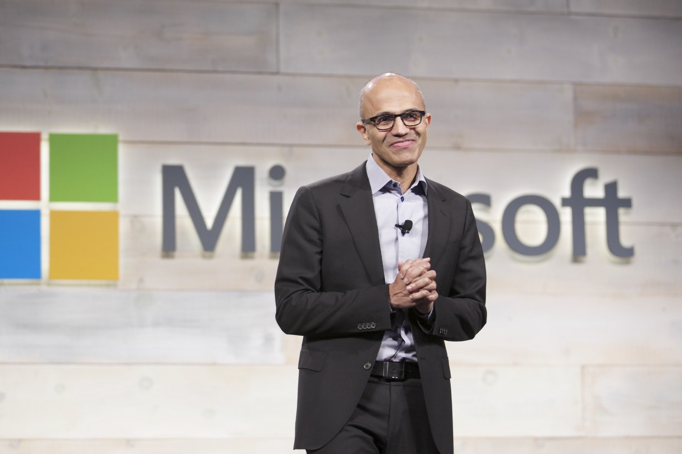 Microsoft CEO Satya Nadella speaks in front of a Microsoft logo.